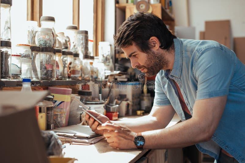 Giovane artigiano che utilizza una compressa nel suo studio di falegnameria fotografia stock