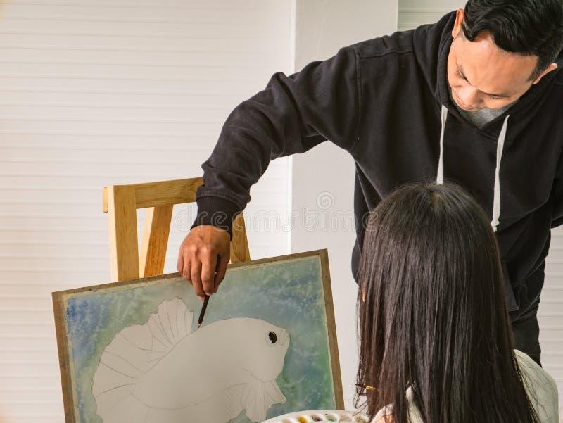 Giovane artista asiatico bello Teaching di colore di acqua o dell'uomo come dipingere e studente Learning dell'artista la classe fotografia stock libera da diritti