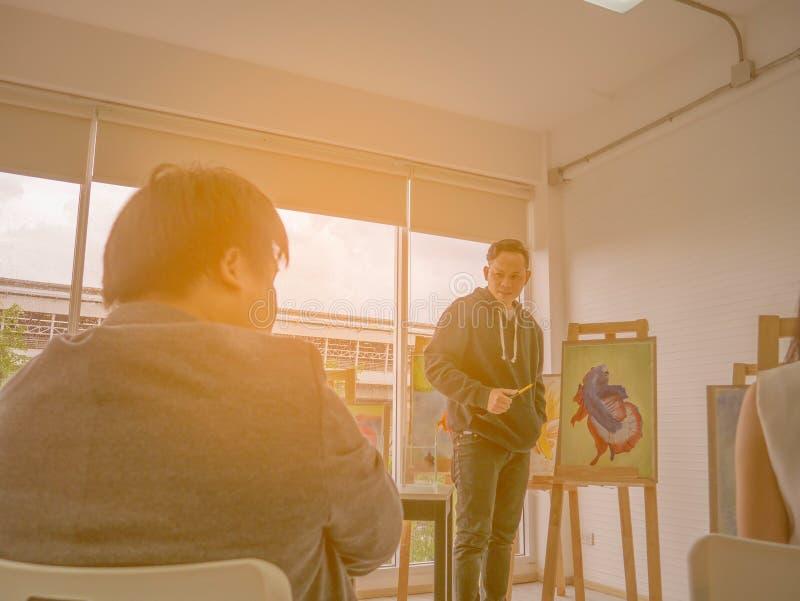 Giovane artista asiatico bello Teaching di colore di acqua o dell'uomo come dipingere in studio fotografia stock libera da diritti