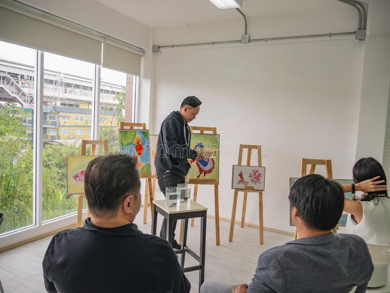 Giovane artista asiatico bello Teaching di colore di acqua o dell'uomo come dipingere in studio immagini stock libere da diritti