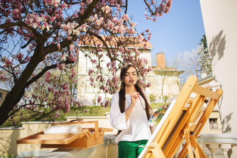 Giovane artista castana della donna che tiene in mani una spazzola e una tavolozza Vicino lei l'albero della magnolia e la varia  immagine stock