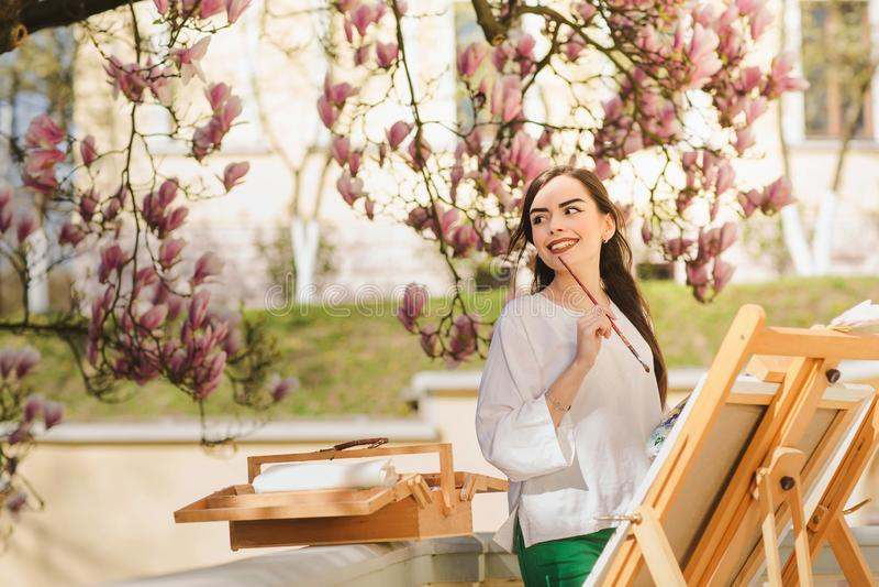 Giovane artista castana della donna che tiene in mani una spazzola e una tavolozza Vicino lei l'albero della magnolia e la varia  fotografia stock