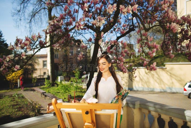 Giovane artista castana della donna che tiene in mani una spazzola e una tavolozza Vicino lei l'albero della magnolia e la varia  fotografie stock libere da diritti