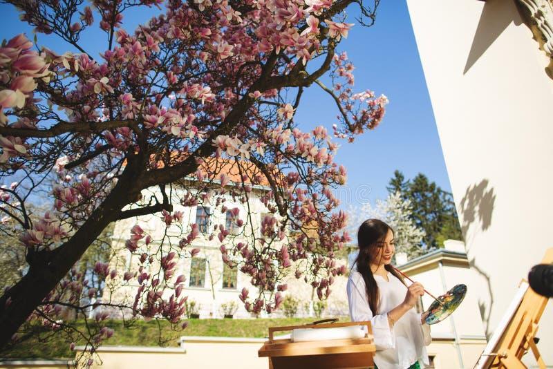 Giovane artista castana della donna che tiene in mani una spazzola e una tavolozza Vicino lei l'albero della magnolia e la varia  immagini stock libere da diritti