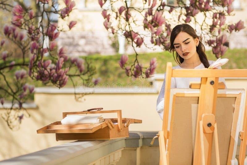 Giovane artista castana della donna che tiene in mani una spazzola e una tavolozza Vicino lei l'albero della magnolia e la varia  immagine stock libera da diritti