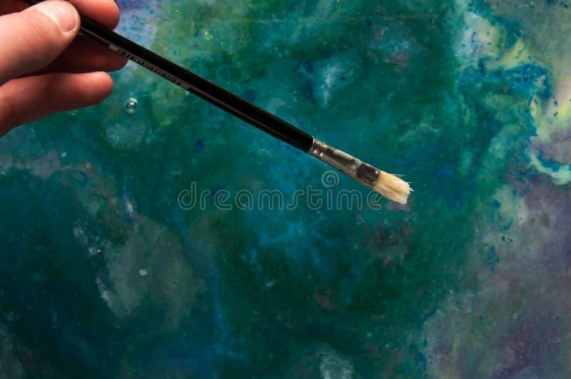 Giovane artista che tiene un pennello, miscela delle pitture ad olio nei precedenti fotografie stock libere da diritti