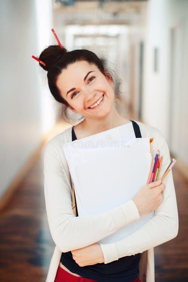 Giovane artista di disegno femminile castana caucasico del progettista della studentessa in corridoio dell'universit? dell'istitu immagini stock libere da diritti
