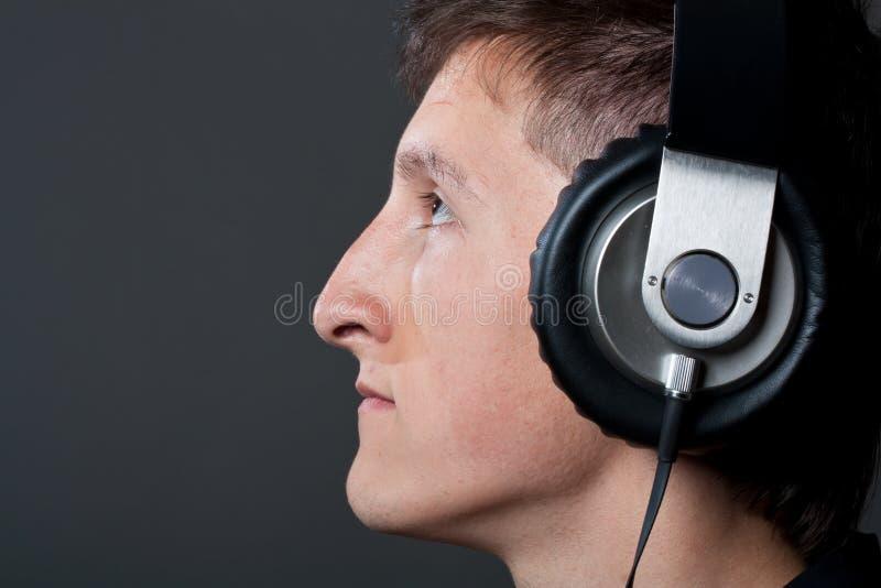 Giovane ascolto della persona maschio immagine stock