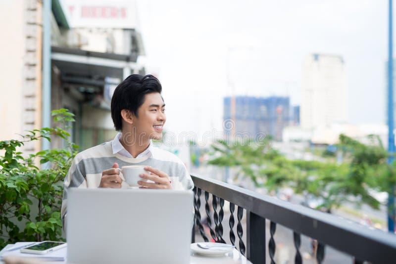 Giovane asiatico bello che lavora al computer portatile e che sorride mentre enj immagine stock libera da diritti