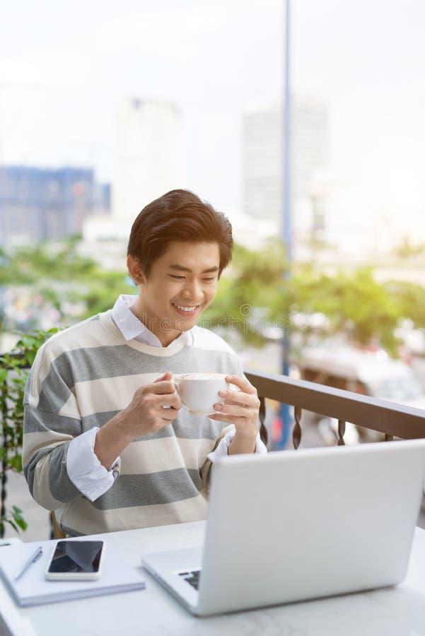 Giovane asiatico bello che lavora al computer portatile e che sorride mentre enj fotografie stock