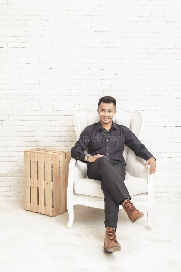 giovane asiatico casuale che esamina macchina fotografica mentre sedendosi ai decori immagine stock