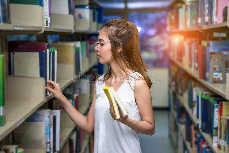 Giovane asiatico della ragazza dello studente che trova studio del libro fotografia stock libera da diritti