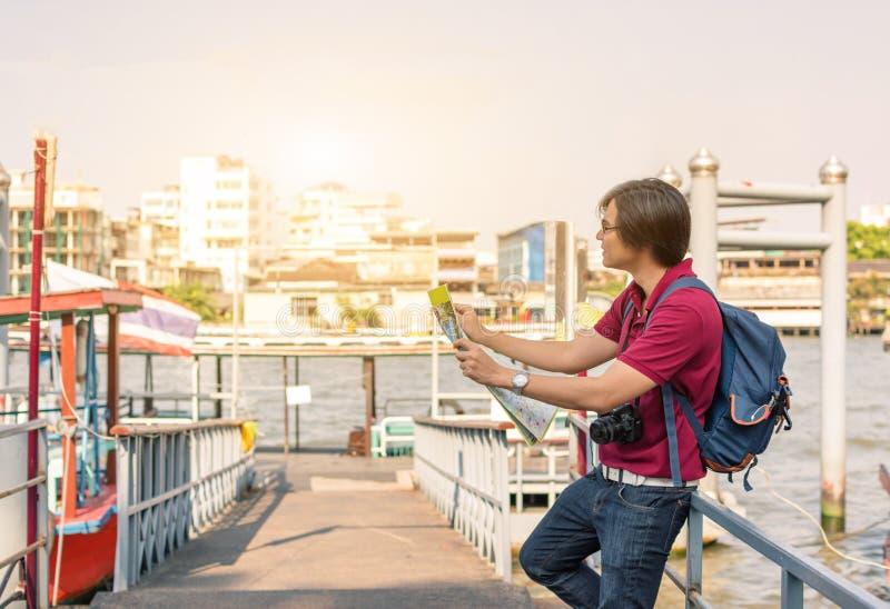Giovane asiatico dello zaino come turista che esamina il travell della mappa fotografia stock libera da diritti