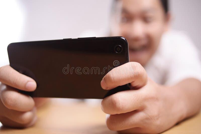 Giovane asiatico divertente Guy Playing Games sullo Smart Phone della compressa immagini stock