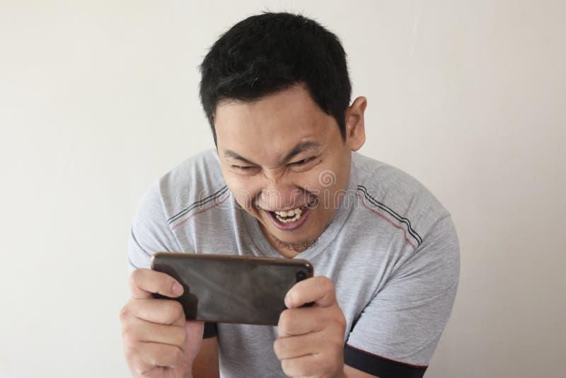 Giovane asiatico divertente Guy Playing Games sullo Smart Phone della compressa fotografie stock