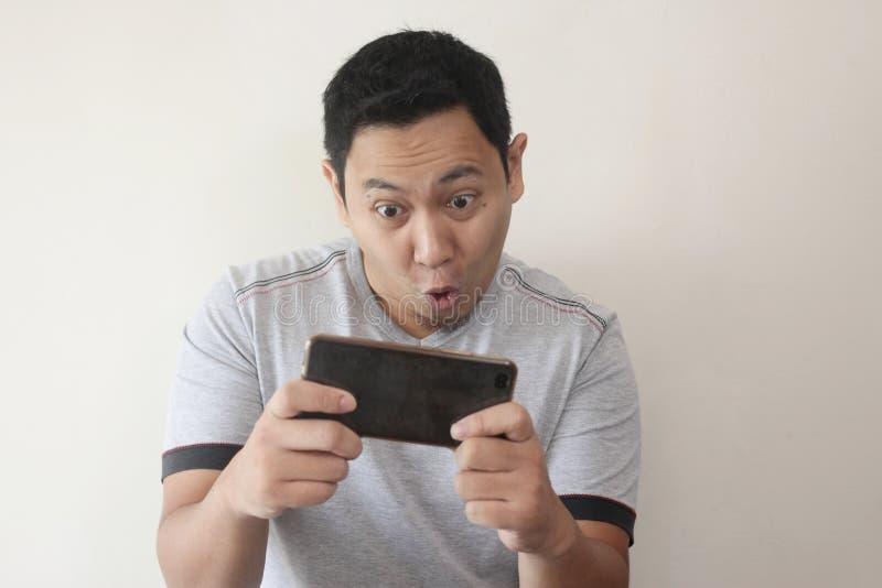 Giovane asiatico divertente Guy Playing Games sullo Smart Phone della compressa fotografia stock