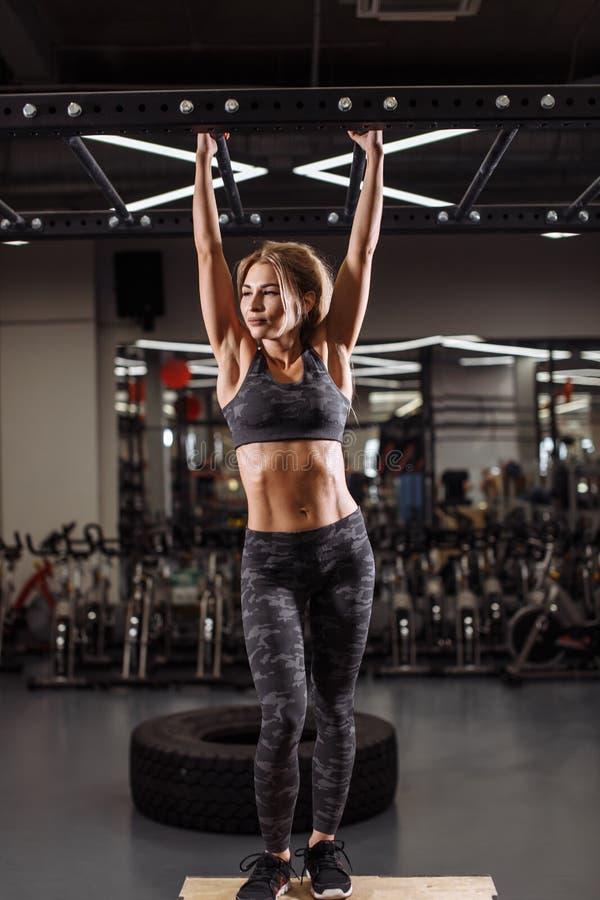 Giovane atleta attraente biondo che ha sfer di resto che tira su esercizio fotografia stock libera da diritti