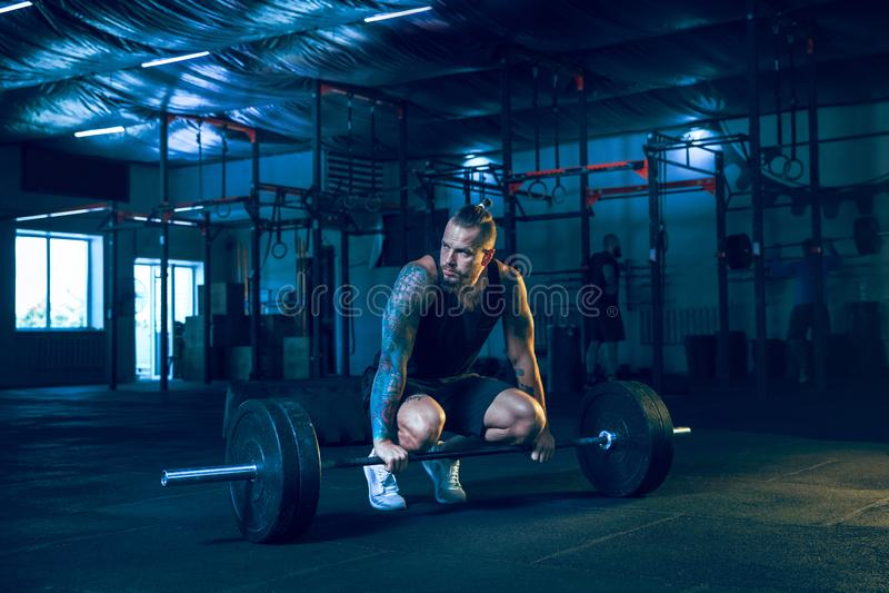 Giovane atleta in buona salute dell'uomo che fa esercizio nella palestra immagine stock