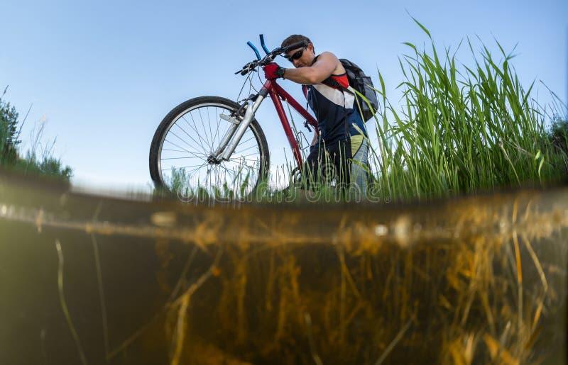 Giovane atleta che attraversa il fiume fotografia stock