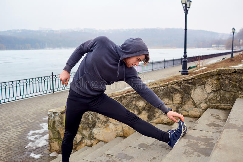 Giovane atleta che fa funzionamento di allenamento che allunga prima dell'correre dentro fotografia stock libera da diritti