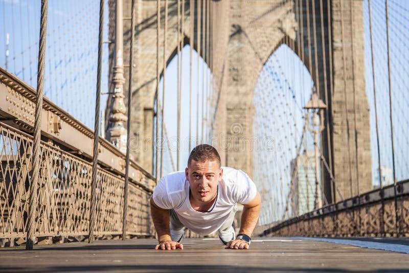 Giovane atleta che fa i piegamenti sulle braccia sul ponte di Brooklyn fotografia stock libera da diritti