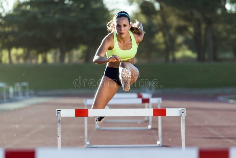 Giovane atleta che salta sopra una transenna durante l'addestramento sul trac della corsa immagine stock