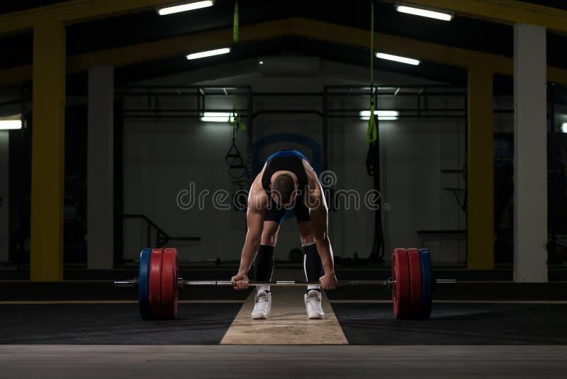 Giovane atleta che si prepara per l'addestramento di sollevamento pesi immagini stock