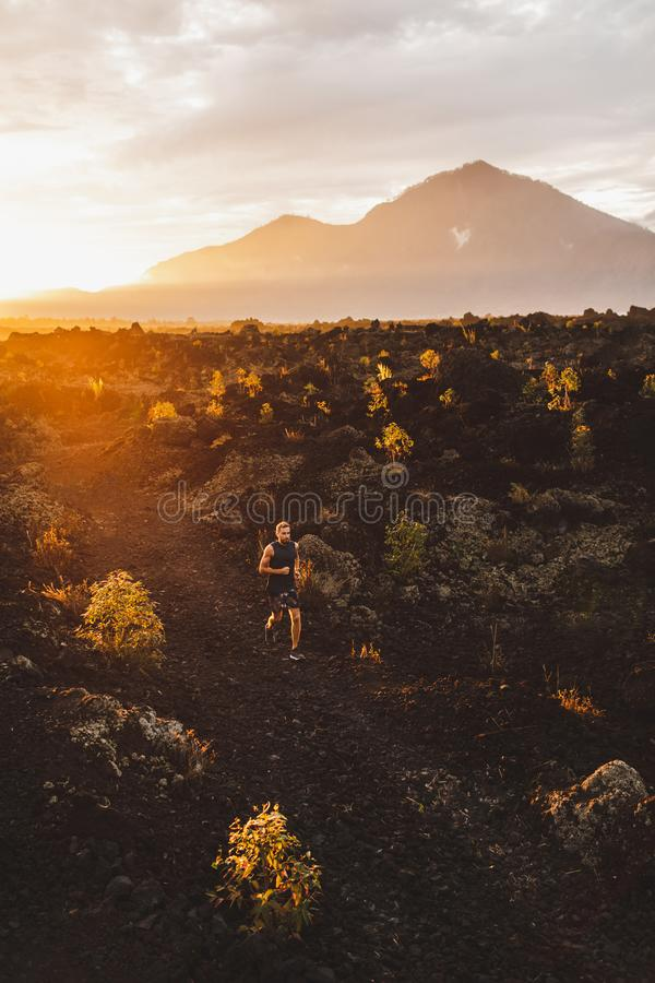 Giovane atleta che trailrunning in montagne all'alba immagini stock libere da diritti