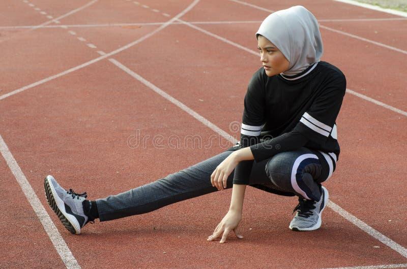 Giovane atleta con hijab che allunga e che si scalda prima dell'correre fotografia stock