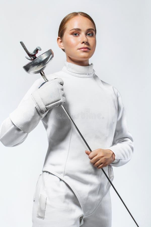 Giovane atleta dello schermitore che dura recintando costume tenuta della spada Isolato su priorità bassa bianca immagine stock libera da diritti