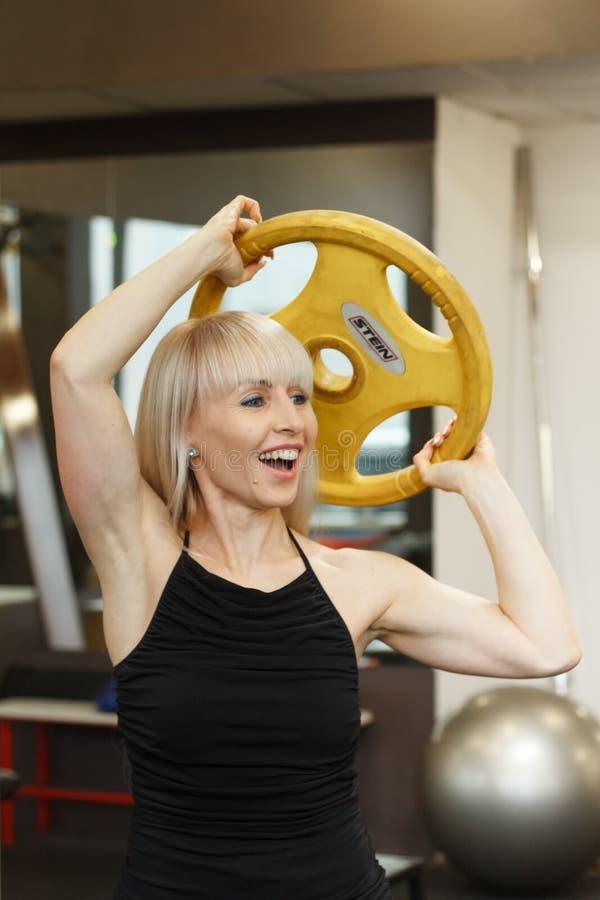 Giovane atleta femminile biondo che fa gli esercizi di sollevamento pesi fotografie stock libere da diritti