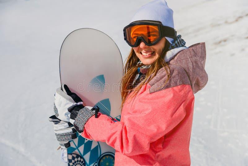 Giovane atleta femminile sorridente con lo snowboard nell'inverno fotografie stock