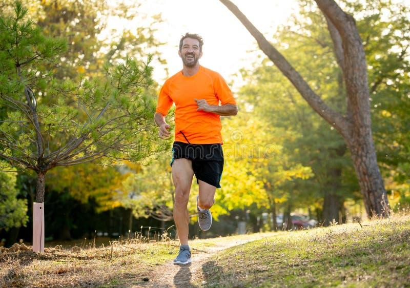 Giovane atletico che corre nella natura al tramonto in autunno nello stile di vita sano di forma fisica immagini stock