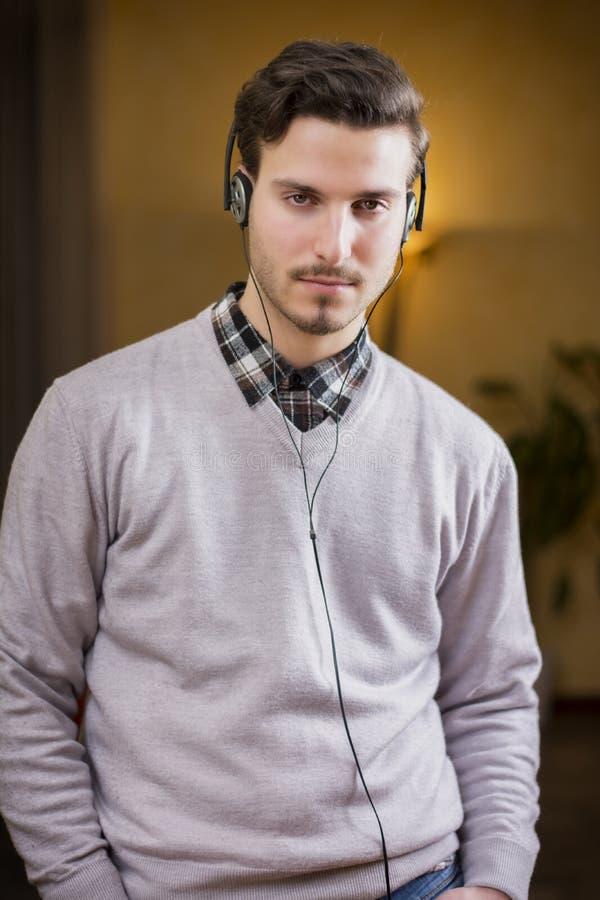 Giovane attraente che ascolta la musica sulle cuffie a casa fotografia stock