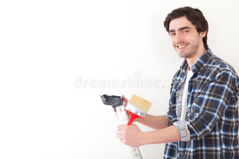 Giovane attraente che dipinge una parete nel suo nuovo piano fotografia stock libera da diritti