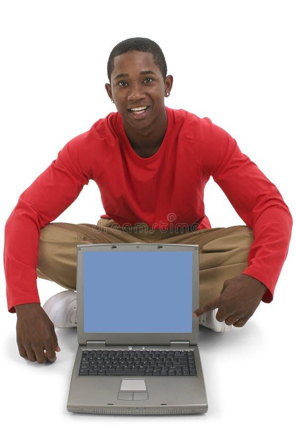 Giovane attraente che indica lo schermo del computer portatile fotografia stock