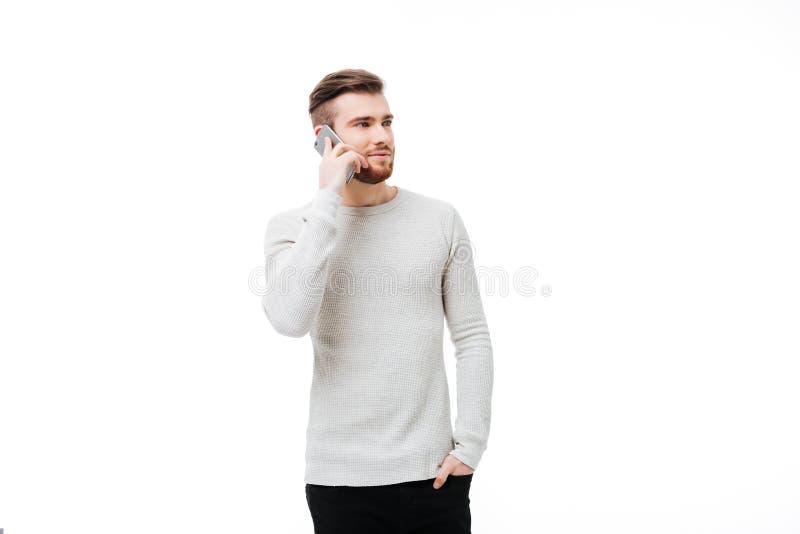 Giovane attraente che parla sul telefono e che distoglie lo sguardo isolato fotografia stock libera da diritti