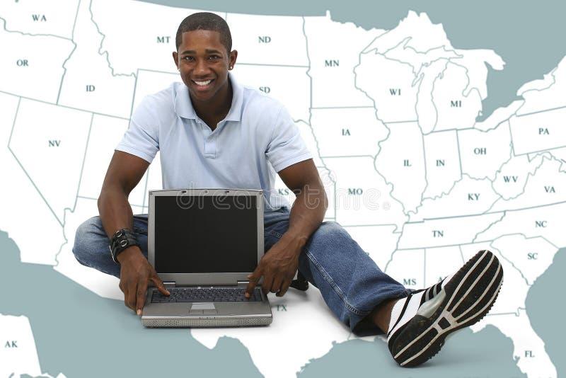 Giovane attraente che si siede sul pavimento con il computer portatile immagine stock libera da diritti