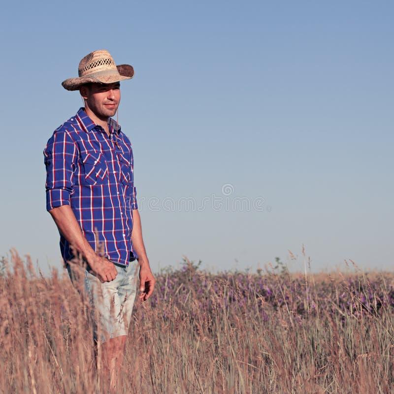 Giovane attraente che sta in un campo cowboy fotografia stock