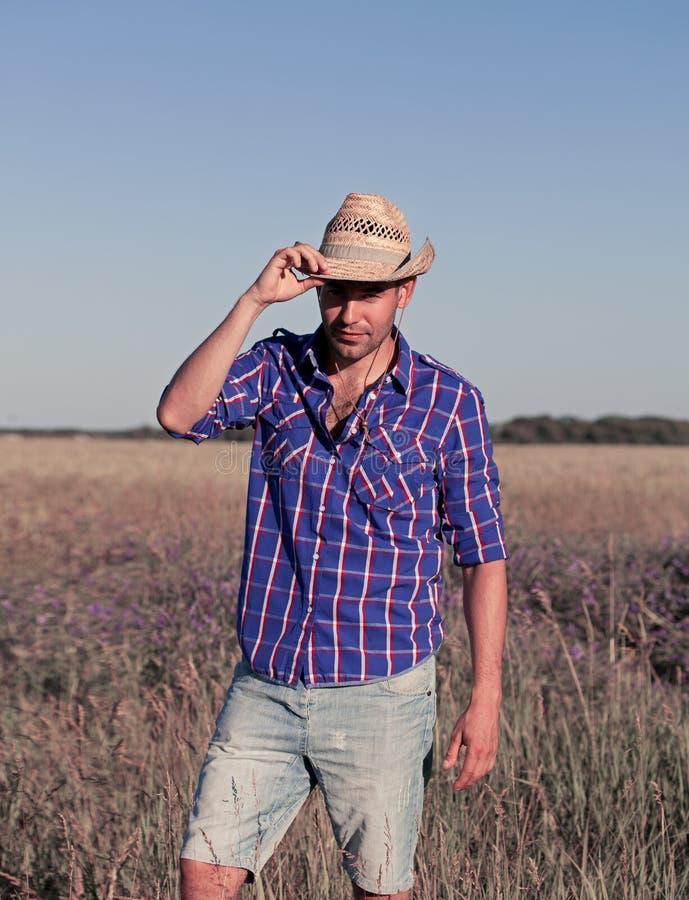 Giovane attraente che sta in un campo cowboy immagine stock libera da diritti