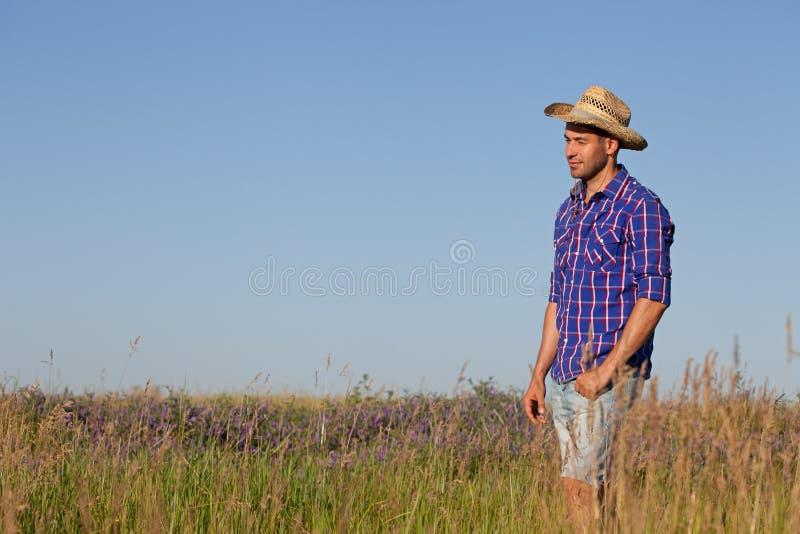 Giovane attraente che sta in un campo cowboy fotografie stock