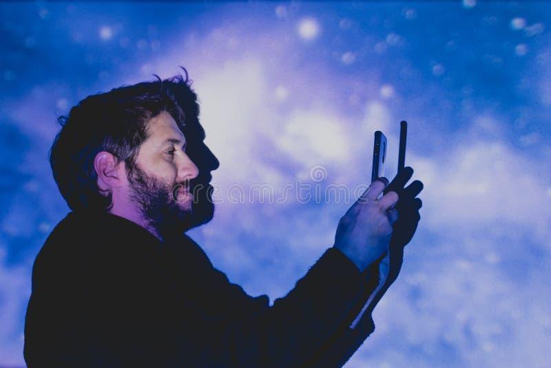 Giovane attraente con la barba che prende le immagini in un ambiente futuristico fotografie stock libere da diritti