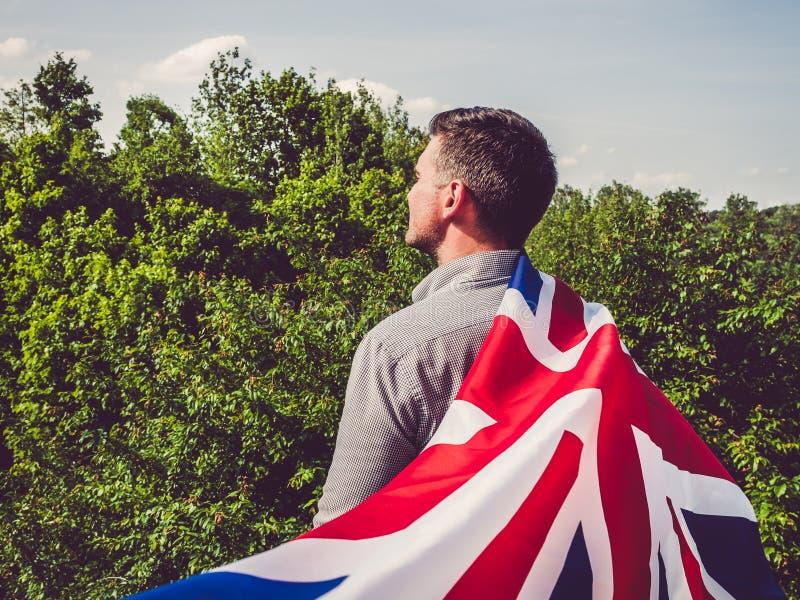 Giovane attraente e che ondeggia una bandiera britannica fotografia stock