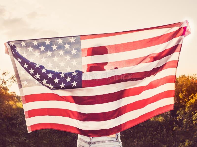 Giovane attraente e che tiene una bandiera degli Stati Uniti fotografia stock