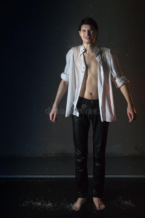 Giovane attraente in vestiti bagnati bianchi in piccolo stagno nell'ambito delle gocce della pioggia Foto dello studio fotografie stock libere da diritti