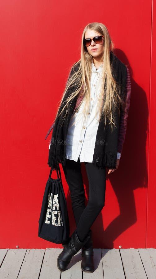 Giovane attrezzatura d'avanguardia bionda stupefacente di usura di donna, vetri alla moda Su fondo rosso, all'aperto Streetstyle immagine stock