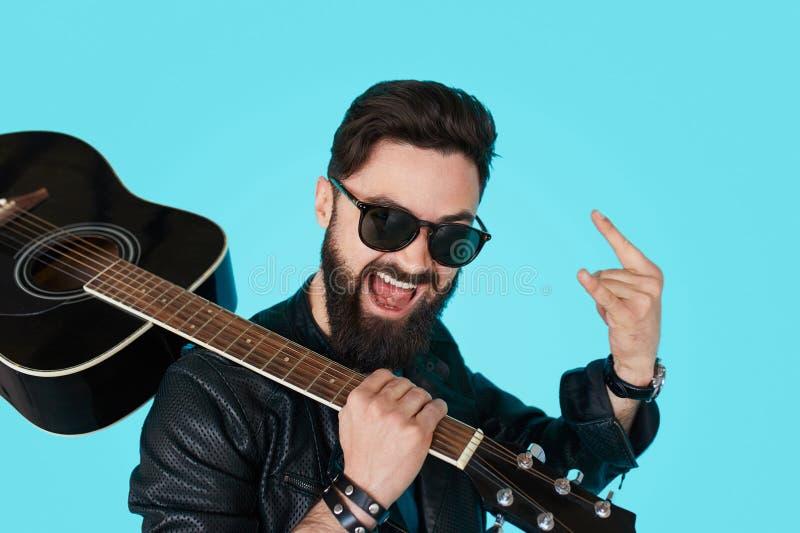 Giovane attuatore punk felice con una chitarra e gli occhiali da sole scuri immagine stock libera da diritti