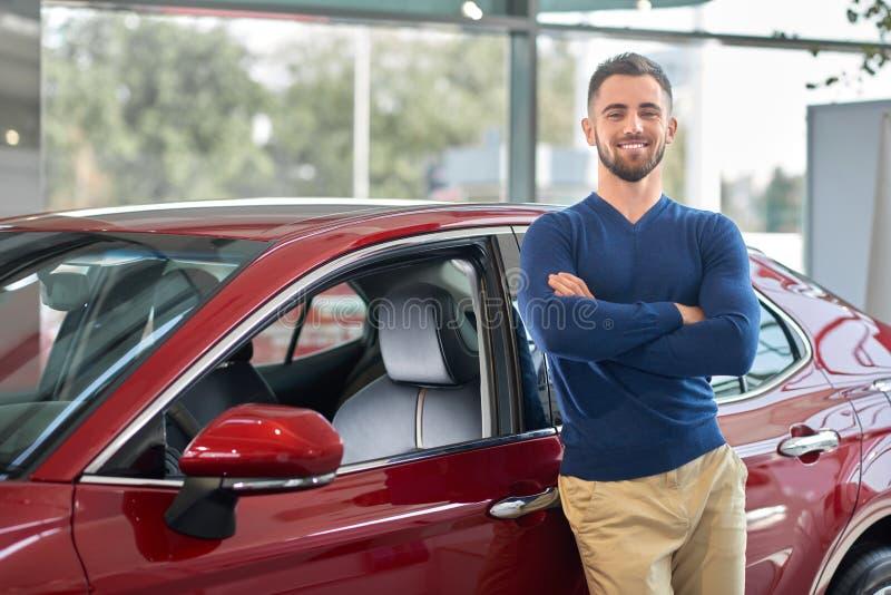 Giovane autista attraente che sorride vicino al suo nuovo veicolo fotografia stock libera da diritti