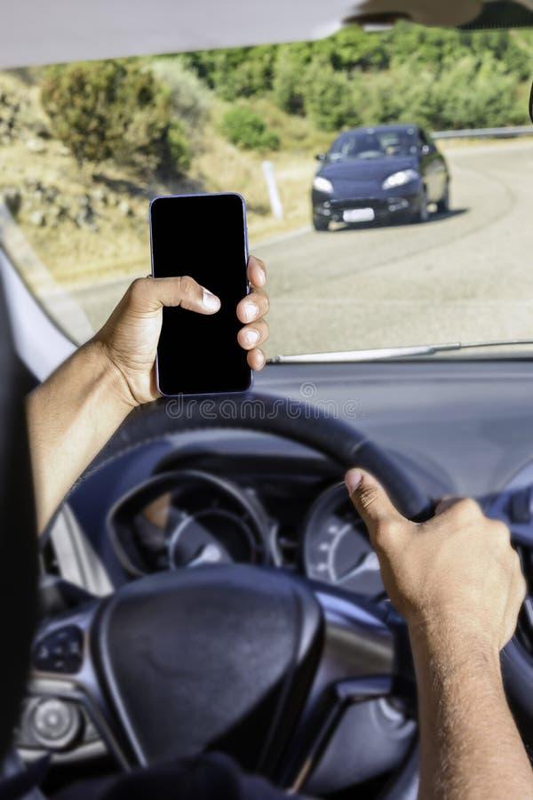 Giovane autista, facendo uso dello smartphone, sulla strada nell'automobile immagini stock libere da diritti