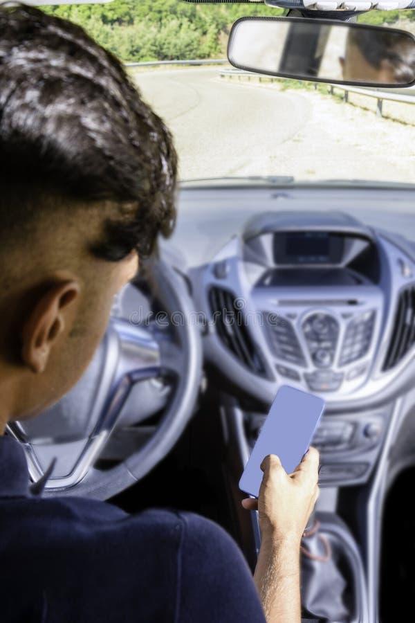 Giovane autista, facendo uso dello smartphone, sulla strada nell'automobile fotografie stock libere da diritti
